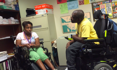 a man and woman, both in wheelchairs, have a conversation