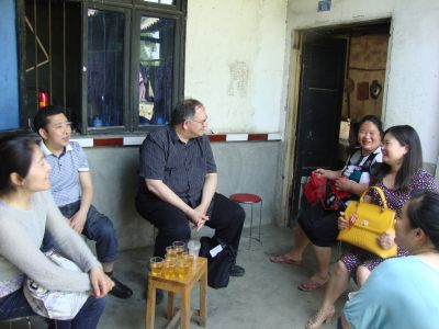 a group of people in China sit outside of a home having a conversation