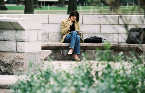 woman sitting on bench reading