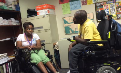 A man and woman, each in a wheelchair, are having a conversation