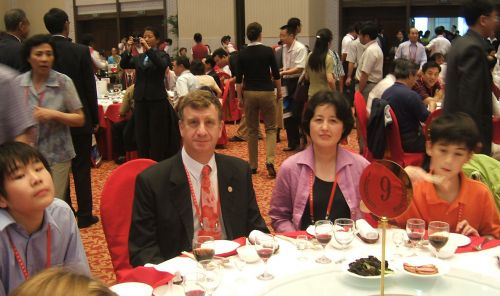 William Alford and YuanYuan Shen posing for photo while sitting at dinner table in Harbin.