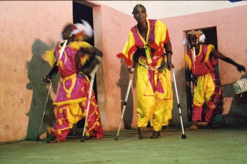 Colorfully dressed women on crutches
