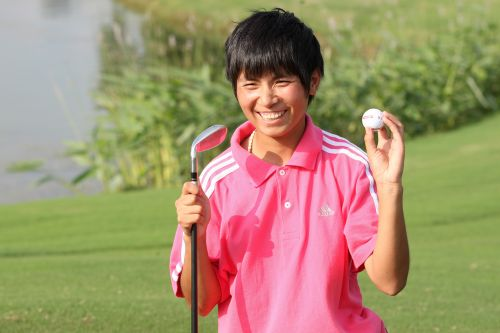 boy in pink shirt standing on putting green holding golf club and golf ball