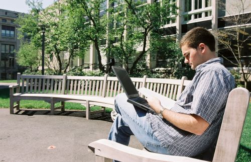 Man sitting on bench with laptop