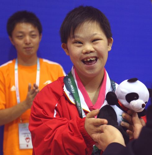 young boy holding special olympics medal and stuffed panda toy with boy in orange shirt looking on